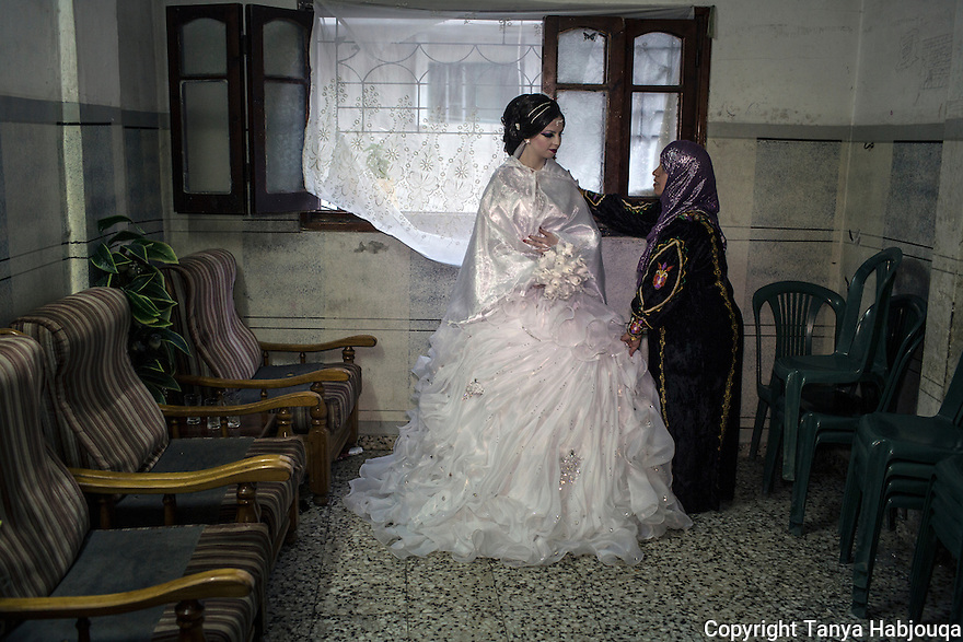 A mother prepares to say goodbye to her daughter,  as they await the groom to come and take the bride to the wedding party.