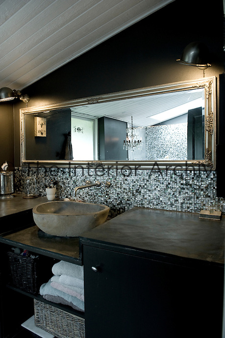 A long mirror above the stone washbasin gives the bathroom a more spacious feeling and the splash back, like the wall is lined with mother-of-pearl mosaic tiles
