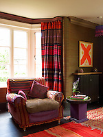 An armchair upholstered in a striped patchwork fabric stands in front of a bay window dressed with tartan curtains