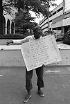 A woman cries out her sermon while holding several home made religious signs on a Charlotte, NC street corner. 6 Aug 2010 Scott LePage/SSA