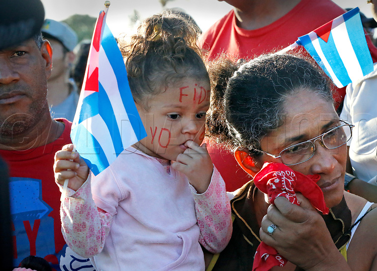 Cubans react after seeing the funeral procession carrying the ashes of Fidel Castro on the road to Cemeterio Santa Ifigenia in Santiago de Cuba on Sunday, December 4, 2016