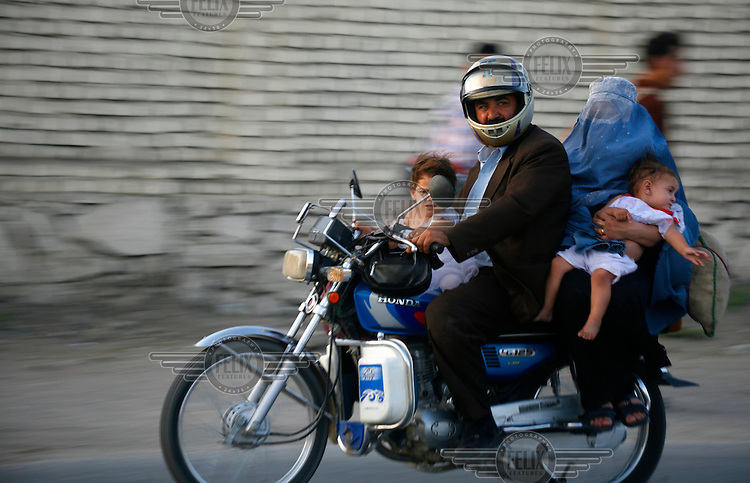 ©Travis Beard / Argusphotography / Picturetank.An Afghan man travels by motorcycle with his wife and kids after going shopping. In the spring of 2007 Jeremy and Travis founded the first ever motorcycle club in Afghanistan: the Kabul Knights Motorcycle Club. Since then they have recruited over 10 members, both male and female, both international and local. They ride every friday and usually head outside Kabul in neighbouring districts.