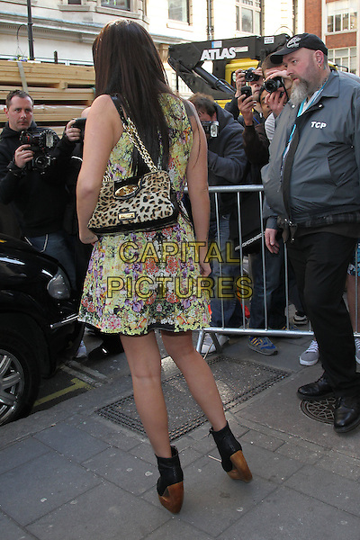 Tulisa Contostavlos at the studios of BBC Radio 1, London, England..April 2nd, 2012.full length yellow purple red floral print dress leopard print bag purse black ankle boots shoes wood wooden heel platform fans photographers back behind rear .CAP/HIL.©John Hillcoat/Capital Pictures .