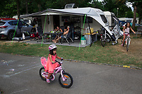 Switzerland. Canton Ticino. Tenero. Camping Campofelice. Family's lunch time. Two young girls ride their bicycles. A caravan, travel trailer, camper or camper trailer is towed behind a road vehicle to provide a place to sleep which is more comfortable and protected than a tent. It provides the means for people to have their own home on a journey or a vacation. Campers are restricted to designated sites for which fees are payable. 19.07.2018 © 2018 Didier Ruef