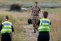 Pictured: Bomb disposal experts and police officers at the scene.<br /> Re: A Bomb Disposal Unit was called after a bomb was discovered at a scrap yard in Skewen near Neath, and then transported to Crymlyn Burrows beach for a controlled explosion in south Wales, UK.