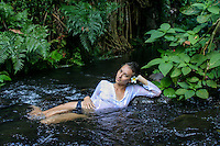 A young local woman with a plumeria in her hair reclines in a stream surrounded by a lush tropical forest, Kane'ohe, O'ahu.