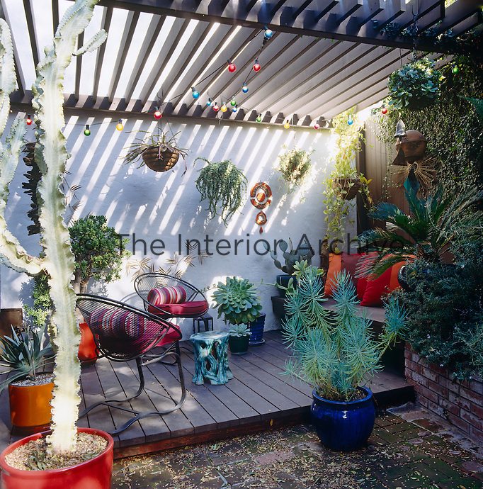 Under a wooden pergola the colorful cushions and plant pots add a touch of fun to courtyard