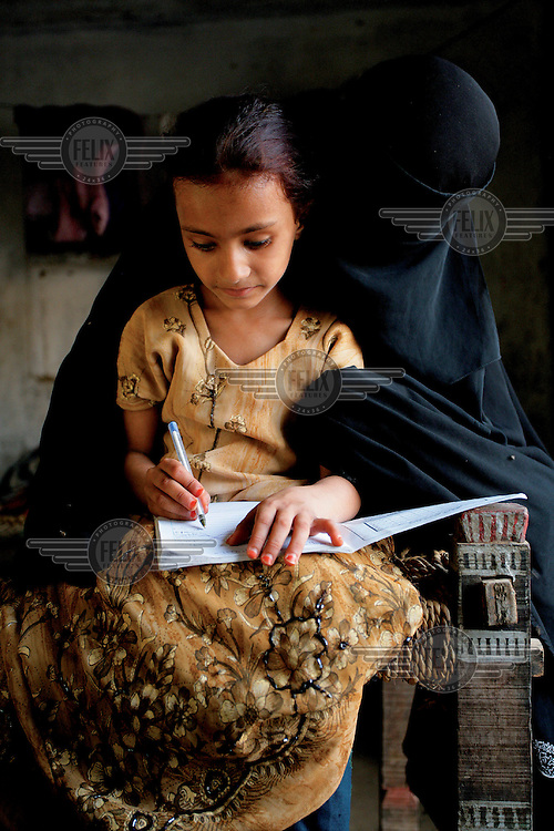 A woman wearing a niqab helps her daughter with her schoolwork, at their home in Zaidia Village in Hodeidah Governorate. While the mother was forced to leave school early, she urges her daughter to attend school and complete her education.