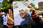 An Egyptian woman holds privately-sponsored posters of incumbent President Abdel Fattah al-Sisi on the the second day of the presidential election at a polling station, in Cairo, Egypt, on March 27, 2018. Egyptians head to the polls in a three-day vote to choose between incumbent Abdel Fattah al-Sisi and candidate Moussa Mostafa Moussa. Photo by Fayed El-Geziry