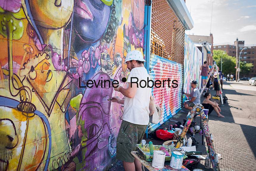 Street artist Cern and other artists at work at the Welling Court Mural Project in the Astoria neighborhood of Queens in New York on Saturday, June 13, 2015. The annual neighborhood event decorates walls in this industrial part of Astoria. The project is crowd-funded and emerging street artists work side by side with established stars.  (© Richard B. Levine)