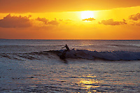 A standup paddler makes the most of the waves at sunset at Launiupoko Beach Park, Maui.