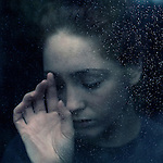 Close up headshot of young woman with sad expression behind glass with water droplets