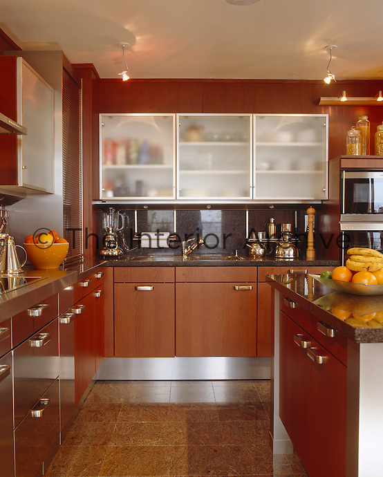 An L-shaped kitchen has chestnut and stainless steel frosted-glass units with a polished granite floor