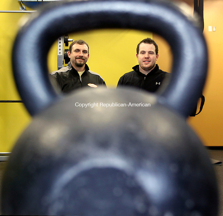 CHESHIRE CT.-14 MAY 2010-051410DA10- Owner of Fitness Express in Cheshire Shawn Stanziale, left and Head Personal Trainer, Patrick O'Sullivan pose through the view of a kettlebell in the gym Friday. <br /> Republican-American  Darlene Douty