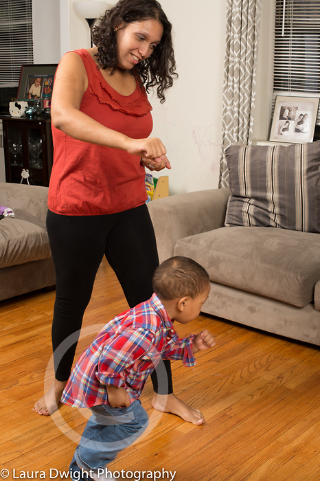 Family at home two year old toddler boy doing exercises with mother