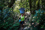 November 10, 2014. &quot;Water it&acute;s the real thing&quot;<br /> A woman comes back from the river where she has been washing the clothes. She doesn&rsquo; t have water at home. The people of Nejapa in El Salvador, have no drinking water because the Coca -Cola company overexploited the aquifer in the area, the most important source of water in this Central American country. This means that the population has to walk for hours to get water from wells and rivers. The problem is that these rivers and wells are contaminated by discharges that makes Coca- Cola and other factories that are installed in the area. The problem can increase: Coca Cola company has expansion plans, something that communities and NGOs want to stop. To make a liter of Coca Cola are needed 2,4 liters of water. &copy;Calamar2/ Pedro ARMESTRE