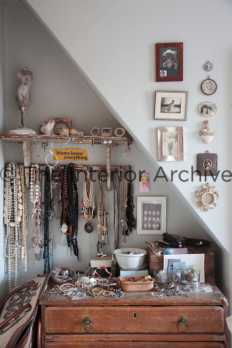 Jewellery hangs from hooks in an alcove. The chest of drawers, is also covered in bits and pieces of jewelley