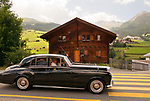 Classic British cars, part of the 24th British Class Car Meeting in St. Mortiz, Switzerland. A car drives through Swiss village of Cunter with views of other villages in the background