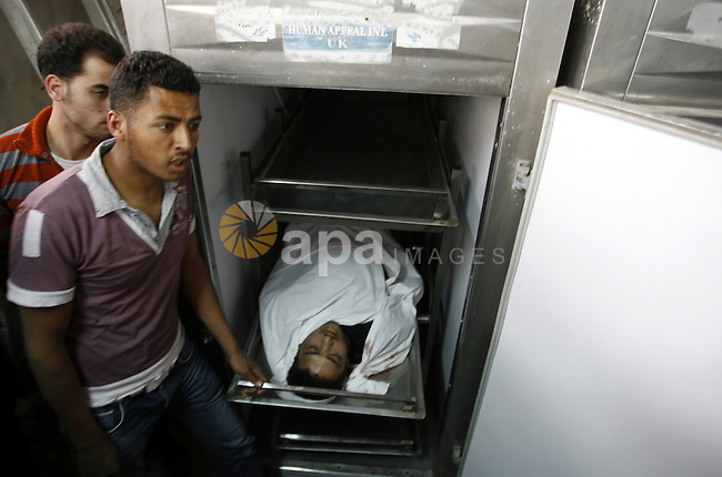 A Palestinian militant body is transported at a hospital Khan Younis in the southern Gaza Strip on March 12, 2012. Israeli air strikes killed two Palestinian militants and wounded 25 civilians in the Gaza Strip on Monday, medical sources said, as cross-border hostilities continued into a fourth day. Photo by Abed Rahim Khatib
