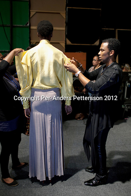 JOHANNESBURG, SOUTH AFRICA  MARCH 09: Designer David Tlale checks models backstage before a show for his designer label at the Joburg Fashion Week on March 09 2012, at the Hyde Park Mall in Johannesburg, South Africa. South Africa's finest designers showed their 2012 Autumn & Winter collections during the 4day event. (Photo by Per-Anders Pettersson)