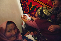 22 year old DInara struggles as an elderly relative of the man who abducted her tries to force a white scarf onto her head. The scarf denotes that she has succumbed to his demands to be married. 3 hours later, she finally accepted his proposal and let her parents know that she was going to stay with Ahmad by a phone-call. However, her parents didn't want to accept the kidnapping and asked Ahmat's parents to propose to her in a formal way. Dinara went back to her home that night. The next day, Ahmad gave her an engagement earring and brought her to his home again. 'I didn't know Ahmad well and didn't want to stay there. But I accepted because this is our tradition' Dinara says. Although illegal, bride kidnapping is common in rural parts of Kyrgyzstan. Each year around 16, 000 women become married after being kidnapped. They are known as 'Ala Kachuu' that translates as 'to grab and run away'. Defenders of the continuation of the practice sight tradition. However, during Soviet Times it was rare, and parents generally arranged marriages..