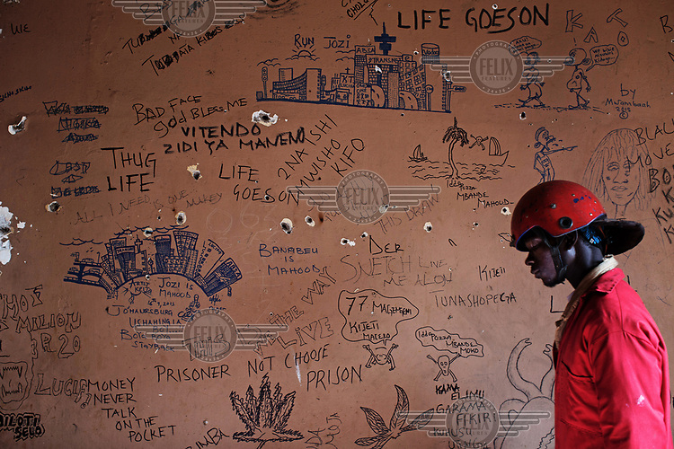 A Red ANt passes a graffiti covered wall in a room in a squatted building on Bree Street. The Red Ants are a controversial private security company often hired to clear squatters from land and so-called 'hijacked' properties.