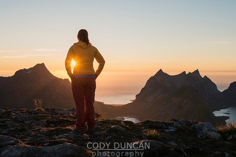 Female hiker watches setting sun from summit of Veinestind, Moskenesøy, Lofoten Islands, Norway