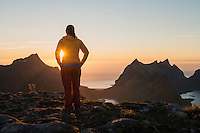 Female hiker watches setting sun from summit of Veinestind, Moskenesøy, Lofoten Islands, Norway