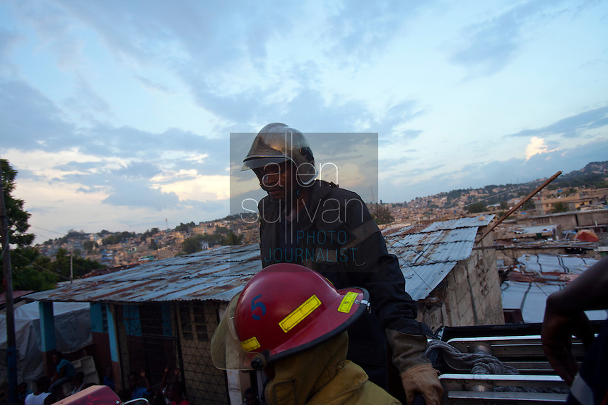Will Mondesir (center) and other firefighters atop a water truck in Port-au-Prince, Haiti return to the city's one fire station after arriving late to an apartment fire. Heavy traffic and narrow streets prevented the crew from getting access to a blaze at a two-story home, so the owners had to put it out themselves with water buckets. A few dozen under-equipped firefighters are tasked with providing fire service to a damaged city of over two million people.