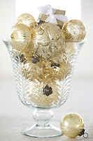 A collection of gold Christmas baubles in a glass vase