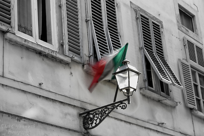 An Italian flag moving the the breeze in a street view with window shutters