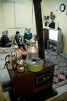 Turkish family watching television behind a traditional soba (coal-burning stove) in istanbul, Turkey