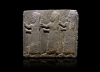 Hittite monumental relief sculpted orthostat stone panel of a Procession Basalt, Kargamis, Gaziantepe, 900 - 700 B.C. Anatolian Civilisations Museum, Ankara, Turkey.<br /> <br /> It is a depiction of three marching female figures in long dress with a high headdress at their head. These women are considered to be the nuns of the Goddess Kubaba. The figures in the front and behind have a bunch of spicy in their right hand while the figure in the middle has an empty right hand. Figures carry objects similar to a sceptre in their left hand. <br /> <br /> Against a black background.