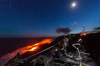 Visitors view the spectacular sight of lava flowing down a cliff and into the ocean at deep dusk, Hawai'i Volcanoes National Park, Hawai'i Island.