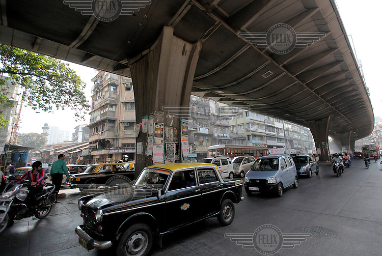 Car driving under an overpass in central Mumbai. Traffic congestion and pollution is a big problem in the city.
