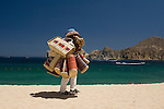 Beach vendor walking on the beach (playa), Cabo San Lucas, Baja California, Mexico
