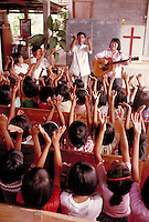 In a rural Christian Church in Thailand, young children sing songs being lead by Christian leaders, child, worship, singing, religions. Christian church, kids singing. Konchin Thailand Christian Church.