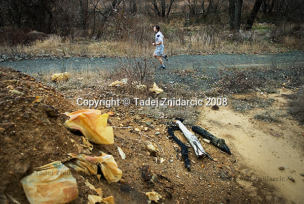 Man runs on a jogging track in northern Mitrovica that was built by the UN next to the toxic tailings, the remnants from processing of lead and zinc ores at the nearby Trepca mining complex.