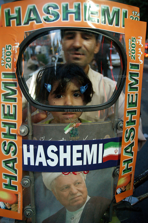 2005..Iran. Tehran. A father and his son show the name of the candidate they support, Ali Akbar Hashemi Rafsanjani, during a demonstration for the 2005 presidential campaign. .Iran. Téhéran. Un père et son fils montrent le candidat qu'ils soutiennent, Ali Akbar Hashemi Rafsanjani, pour l'élection présidentielle de 2005...