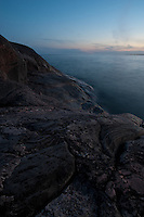 Dusk over Lake Superior, with the granite rocks of the Canadian Shield running down to the blue water.