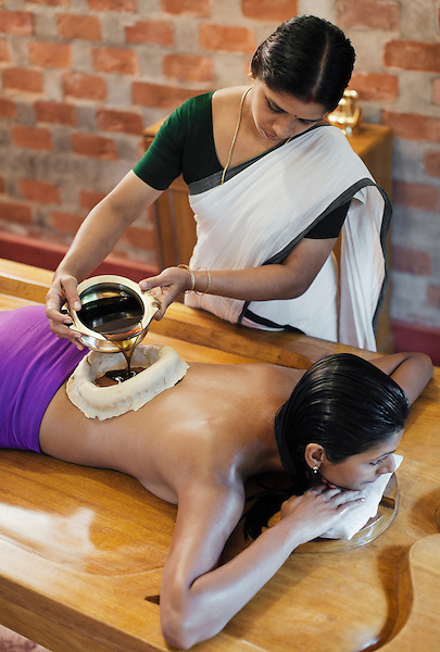 Woman Receiving Kati Vasti, Ayurvedic Oil Treatment, Kairali Ayurvedic Health Resort, Palakkad, Kerala, India. In Kati Vasti, dough made from an herbal mixture is shaped into a ring and placed on the client's lower back. Warm, dosha-specific oil is poured into the ring and remains there for 30 to 60 minutes. This treatment strengthens the vertebral column, pelvic girdle, spinal cord and spinal nerves. It is good for alleviating all types of back pain, including a slipped disc and sciatica.