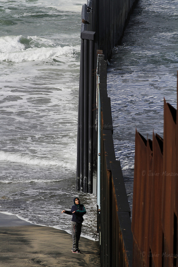 Local residents exercise next to the fence that separates the United States from the border city of Tijuana, Baja California, Mexico on February 9, 2013.  (Javier Manzano / For The Washington Post).