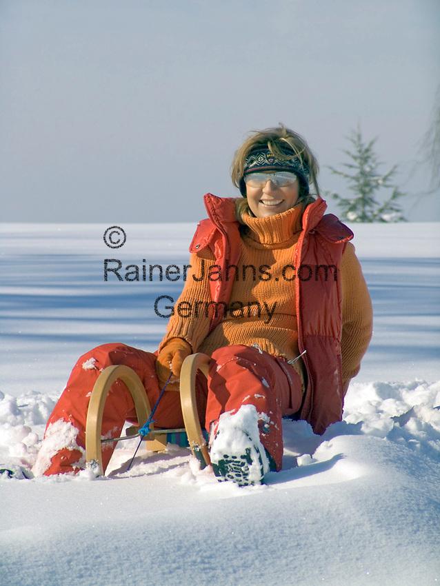 Deutschland,  Frau sitzt auf Schlitten | Germany, woman sitting on a sledge