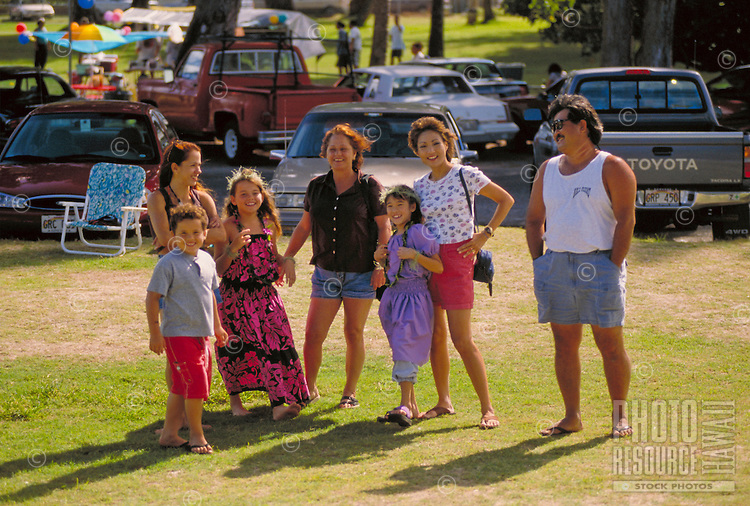 Two families at beach park after hula performance.