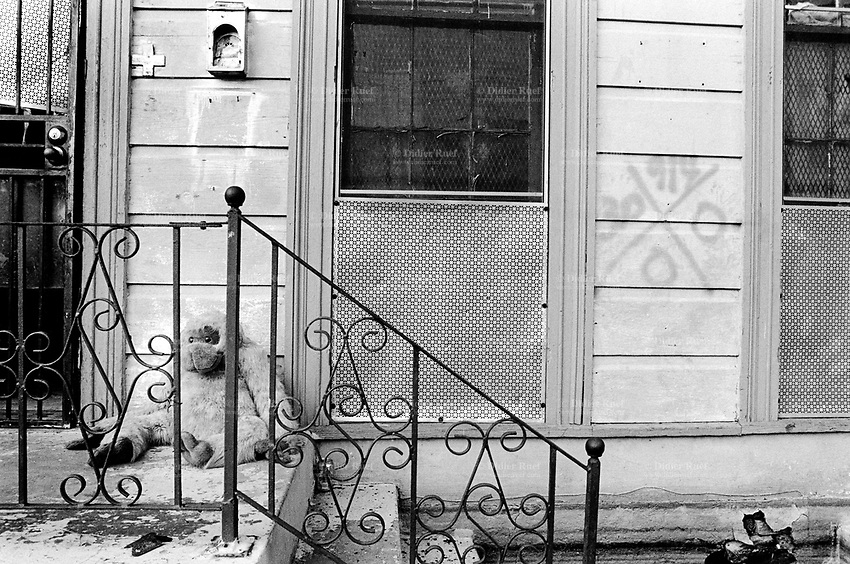 """USA. Louisiana. New Orleans. Orleans Parish. La Harpe Street. Aftermath of hurricane Katrina. The house (villas, detached or personal houses) was flooded and the inhabitants have left the town. The belongings have been destroyed by the water and have to be thrown away, like the monkey child's toy. The New Orleans Police Department has controled the house on august 30 (hand painted cross on the wall) during a """" search and rescue"""" operation if there was any dead people in the house. None was found. Household refuses. Urban  waste. © 2005 Didier Ruef"""