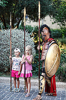 Two girls with an ancient Greek warrior in the streets of Athens, Greece