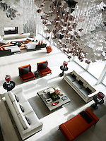 A spectacular custom lighting sculpture acts as a canopy above one social seating group shaped with Christian Liaigre's velvet sofas and spicy red chairs. The soaring double height windows flood the room with light. The fireplace is wrapped in split-face limestone.