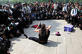 Contorsionist watched by London school children on the South Bank