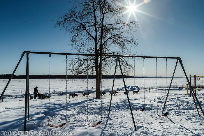 Richie Diehl runs down the road past school playground swings with the Yukon River in the background as he leaves the Nulato checkpoint on Saturday March 12th during the 2016 Iditarod.  Alaska    <br /> <br /> Photo by Jeff Schultz (C) 2016  ALL RIGHTS RESERVED