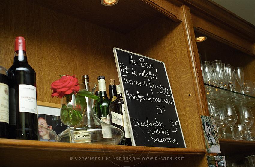 Shelf in a bar with bottles glasses flower and chalk board. Wine bar les Enfants Rouges in Paris. Paris, France.